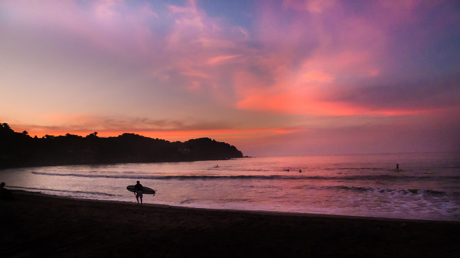 silhoutted surfer in front of sayulita sunset