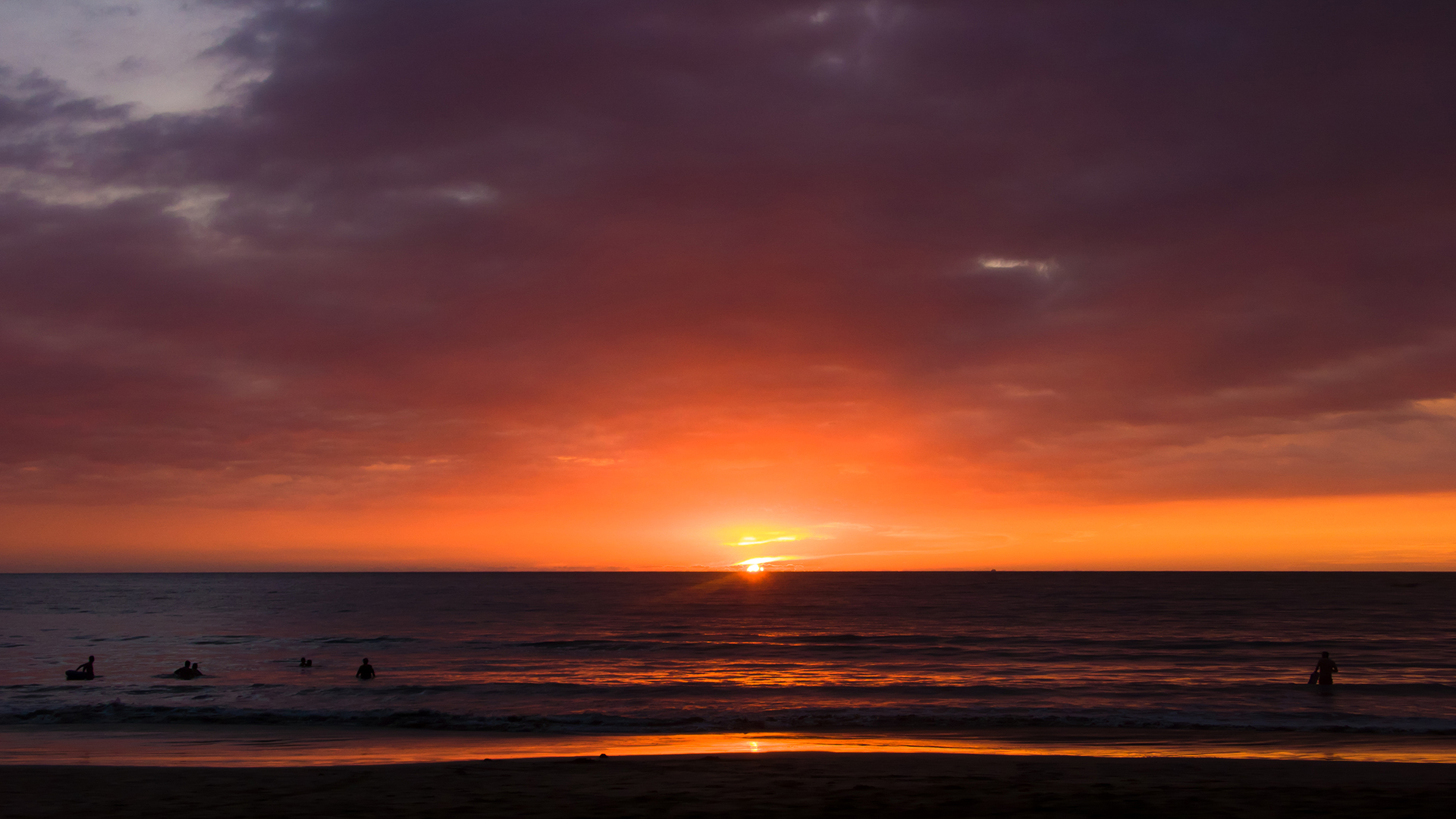 Red sunset over Riviera Nayarit beach with surfers in front